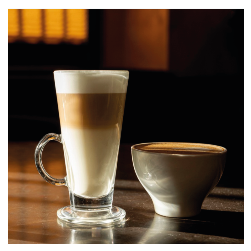 Latte Macchiato im Glas daneben steht ein Cappuccino in der Tasse