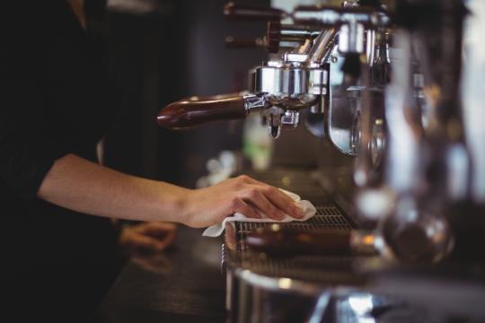 Barista reinigt Kaffeeautomat