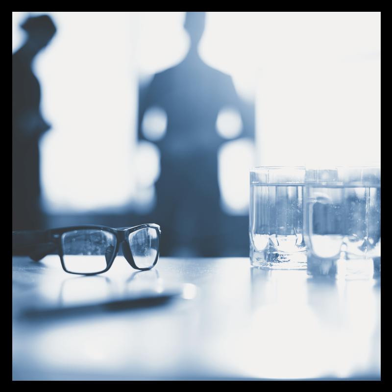 Wasserglaeser auf  Tisch mit einer Brille daneben